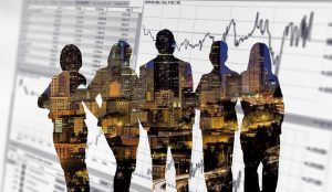 Dark silhouettes of five people that show a city with buildings lit up and the silhouettes are against a background of a line chart trending upwards