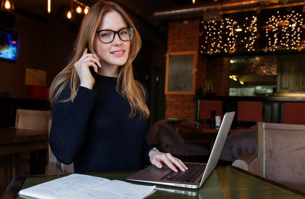 A picture of a business woman on the phone while also on a laptop, pieces of paper lie beside the laptop