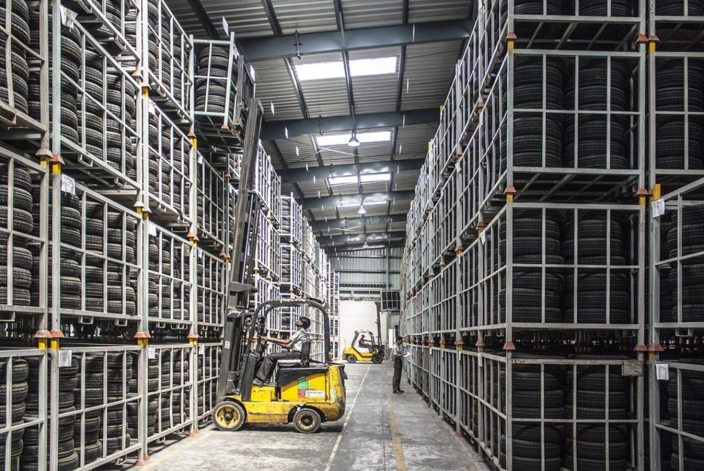 Picture of an aisle of a warehouse where tires are stacked neatly in storage cages up to the ceiling and a forklift driver is taking down one of the cages of tires