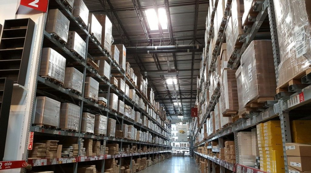 Picture of an aisle of a warehouse where shelving units are stacked with products from floor to ceiling