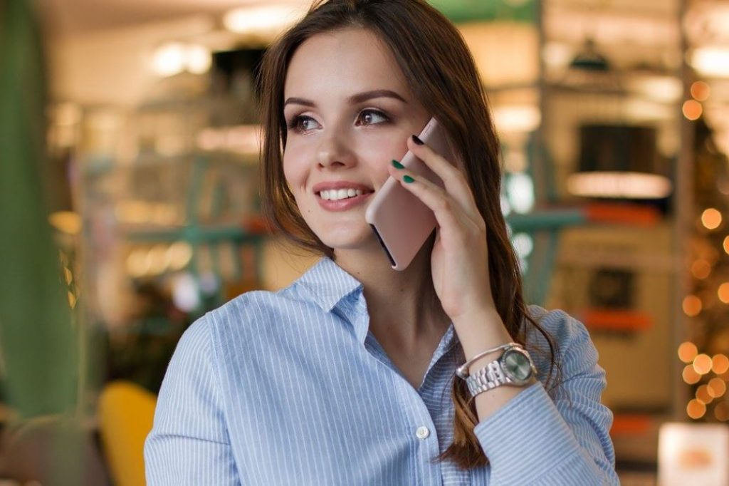 Picture of a business woman smiling on the phone, who is eligible for a loan