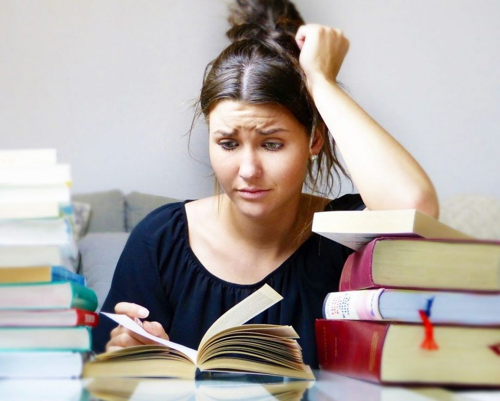 Picture of a woman sitting and looking at a book, surrounded by books, and pulling her hair