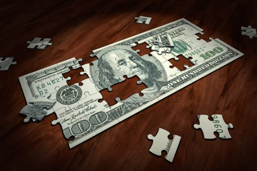 Picture of puzzle pieces forming a 100 dollar bill