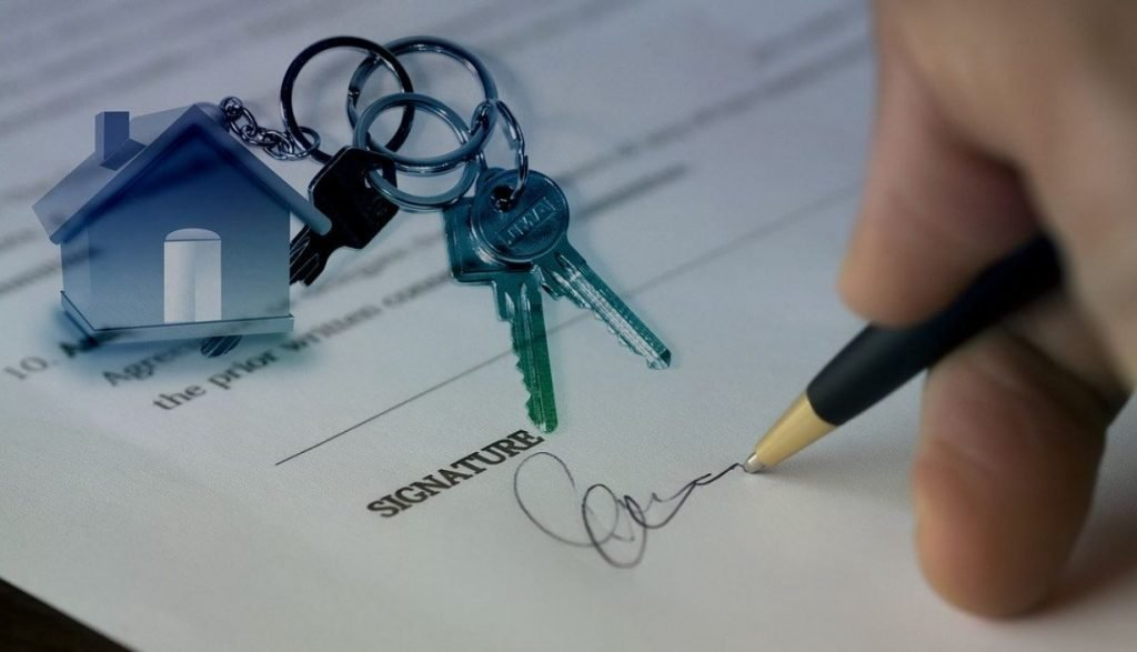 Picture of a hand signing a document with keys on a keychain with a miniature house lying above the signature space on the paper