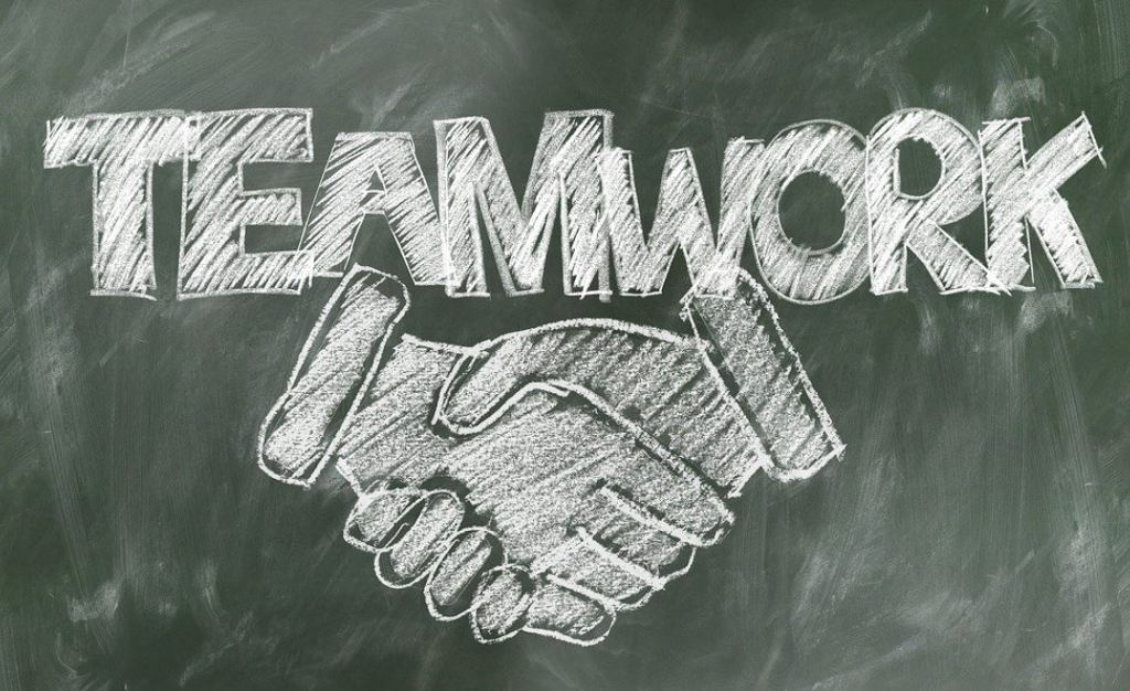 Picture of a chalkboard drawing of a handshake with the word Teamwork above it